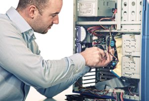 Computer repair services - image of a computer engineering repairing a computer.